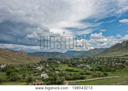 View of the village of Asubulak, Kazakhstan. Beautiful clouds over the village surrounded by mountains. Summer time