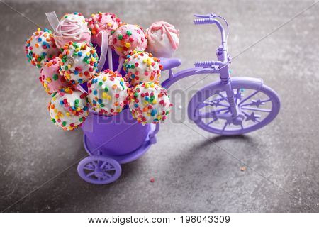 Bright colorful cake pops in decorative bicycle on grey slate background. Selective focus.