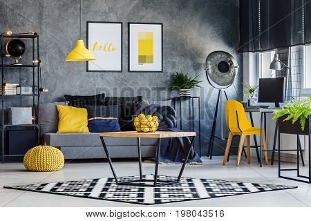 Masculine room decor with yellow lamp chair pouf poster and cushions