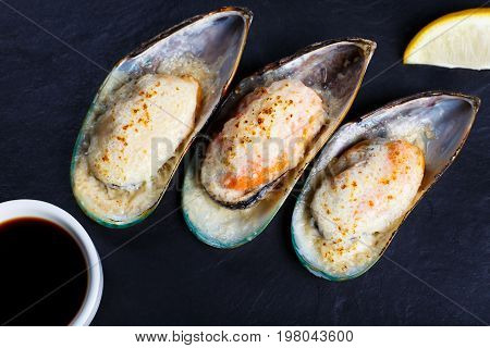 Baked Shellfish Mussels With Soy Sauce And Lemon Served On Black