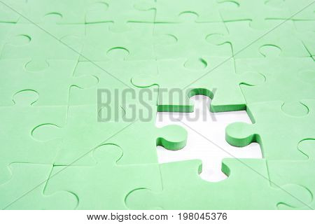 Folded green puzzle with a hole instead of without one element