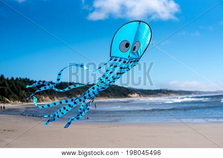 Blue kite with eyes and polka dots being flown at the beach