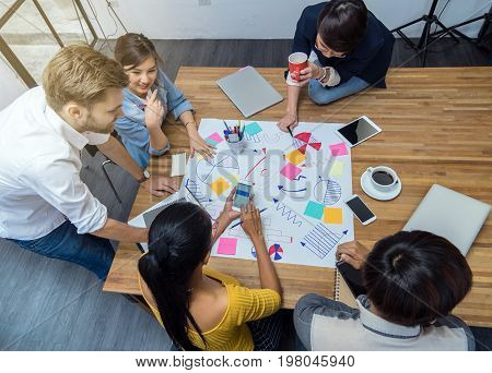 Top view of Group Of Asian and Multiethnic Business people with casual suit working and brainstorming together in the modern Office Top view people business group concept