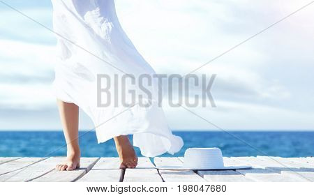 Beautiful legs of a young woman in white skirt on a wooden pier at summer. Vacation, resort and traveling concept.