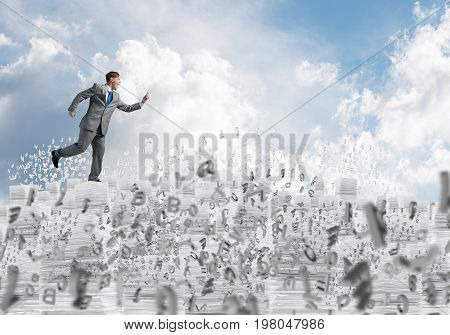 Businessman in black suit running with phone in hand among flying letters with cloudly skyscape on background. Mixed media.
