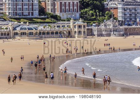 San Sebastian Spain - June 6 2017: People strolling at the La Concha beach in the city of San Sebastian Basque country Spain