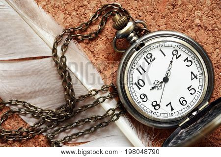 Old pocket watch near feather on cork wooden background