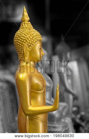 The golden Buddha image in a Thai temple on a black and white background.