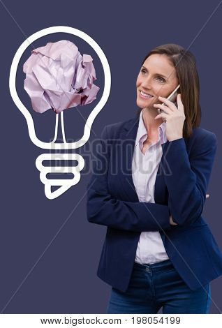 Digital composite of Woman on phone standing next to light bulb with crumpled paper ball