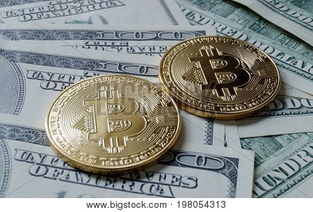 Two symbolic coins of bitcoin on banknotes of one hundred dollars. Exchange bitcoin cash for a dollar.
