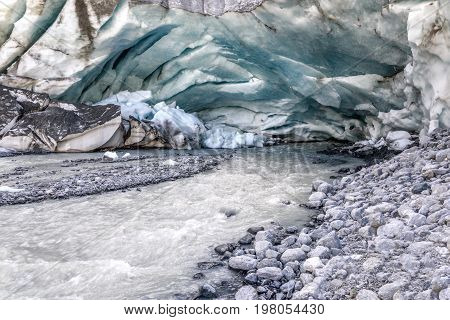 A colorful view of the ice cave in the glacier and the source of the fast mountain river flowing out of the glacier