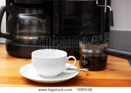 Closeup Of White Coffee Cup Next To Coffee Machine