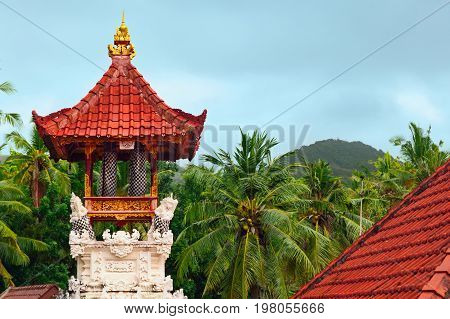 Wooden bells kulkul on traditional belfry with carving on white limestone walls. Balinese hindu temple on jungle and rainy sky background. Nusa Penida island landmarks. Culture of Indonesian people.