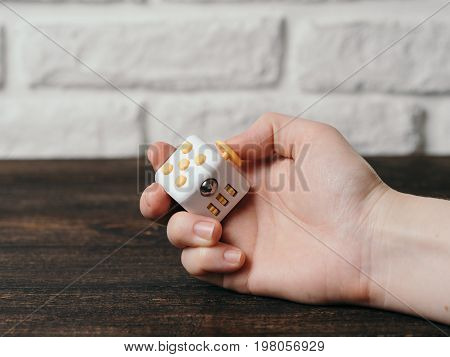 Fidget cube stress reliever in hand over brown wooden background. Fingers antistress toy in hand with copy space.