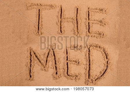 The Med written in soft wet sand on a beach