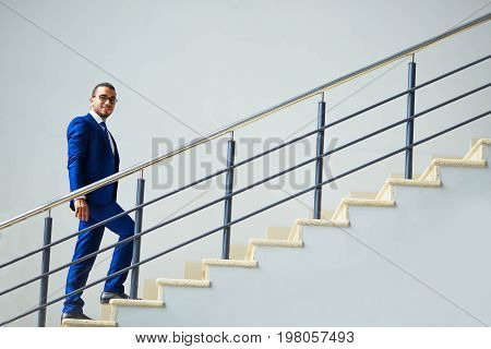 Stairs To Success. Young Smiling Businessman Climbs The Stairs