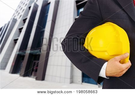 Yellow business holding man helmet background greeting