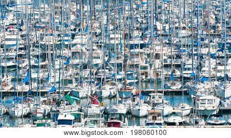 View on busy harbor of french city Marseilles with many private boats and yachts. White ships and blue water. Marseilles Provence France Europe.
