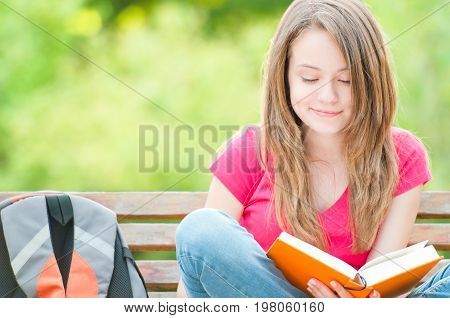beautiful and happy young student girl sitting on bench smiling and reading book. Summer or spring green park in background