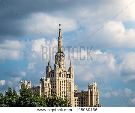 One of Moscow's famous highrises. Blue cloudy sky in background tree in foreground. Summer in Russia.