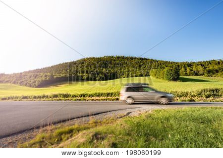 Car on country road in Norway Europe Scandinavia. Auto travel on sunny day. Blue sky with no clouds.