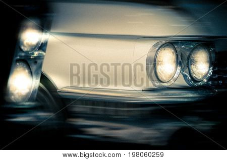 Headlights of a vintage cars. Night scene with motion blur. Grain added.