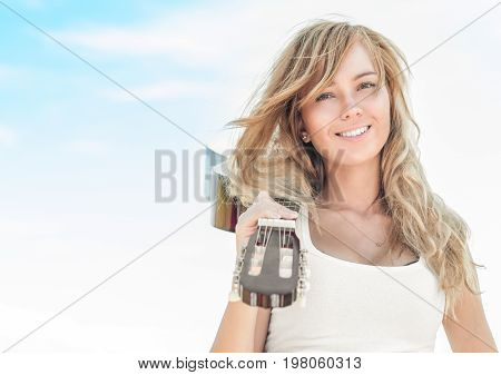 Beautiful smiling girl with guitar on her shoulder and blue sky background. Young happy female musician with fair hair. Music as hobby or lifestyle. Art and freedom.