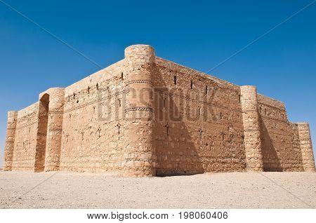 ancient desert castle with blue sky in background in Jordan