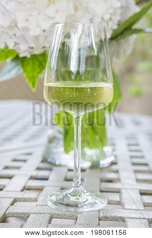 Glass of White on Garden Table with Freshly Cut Hydrangea as Backdrop