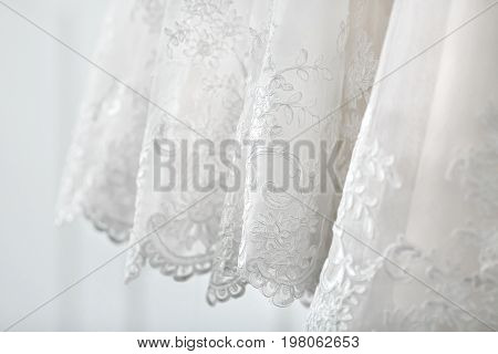 A Bottom Part Of The White Luxury Bridal Dress. Side View. Close-up
