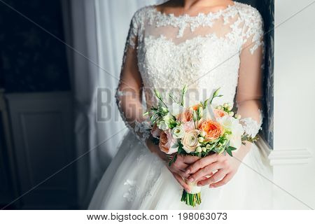 A Beautiful Bride Is Standing Near The Window And Holding A Wedding Bouquet With White Roses And Pea