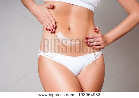 Woman Applying Moisturizer Cream Lotion On Belly.  Woman Wear White Underwear