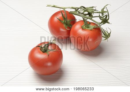 Tomato on branch on white background, red and hite