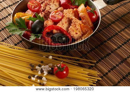 Cooking pan with fried chicken fillet and baked vegetables tomatoes paprica bell peppers garlic and green basil with italian spaghetti and spice seasoning on wooden mat.