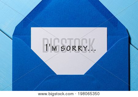 I'm SORRY - message in blue envelope at wooden background