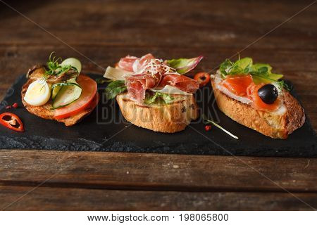 Close up of small canapes laying on black tray. Appetizers with salmon, ham and sprats, decorated with olive, sliced cucumber and avocado