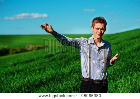 Man On The Field Shows On Elongated Hand Somewhere Far Into Something