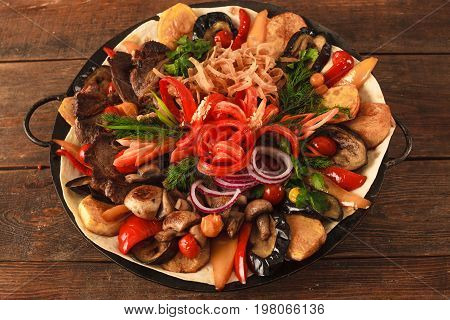 Dish with stewed meat, different kind of vegetables, field mushrooms, laid on lavash and big copper plate, and decorated with sliced onion and pepper. Top view picture on wooden table