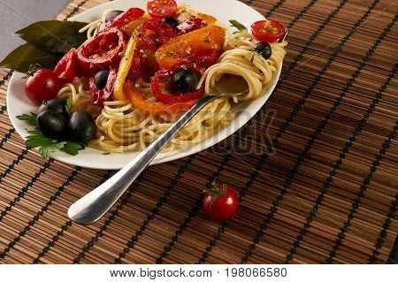 Pasta spaghetti with tomato sauce olives paprica and peppers on plate with fork brown table mat. Healthy and vegetarian food concept. Closeup