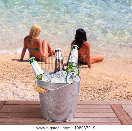 Three unopened bottles of beer inside ice bucket on beach background