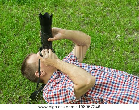Photographer Lies On The Grass And Takes Pictures. Side View