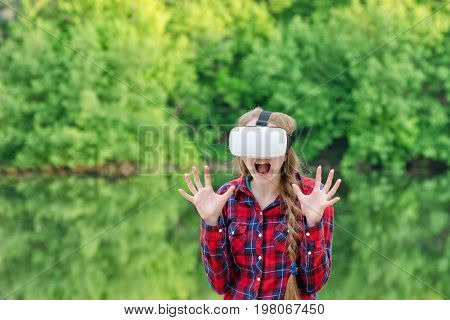 Girl In A Helmet Of Virtual Reality On A Background Of Nature. Fright