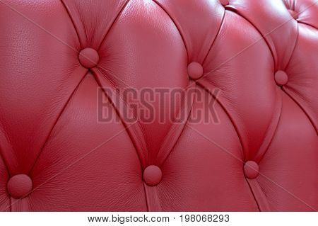 stitch of decorative upholstery of a back of a sofa of red