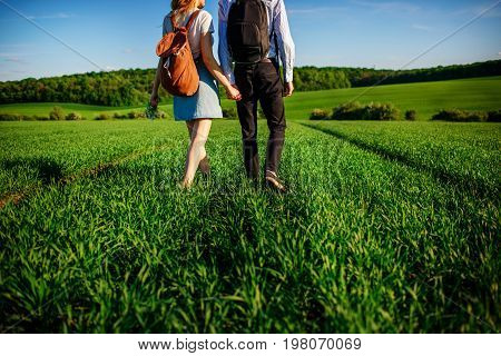 Young Couple Is Strolling Through The Greenfield. Woman And Man Are Holding Each Other By The Hands