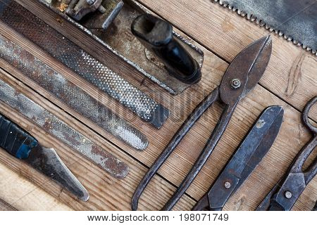 Close up view vintage rusted tools on old wooden table: pliers pipe wrench screwdriver hammer metal shears saws and other