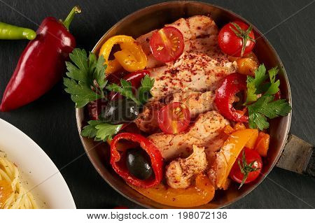 Tasty pasta with cheese fried chicken and red dry wine glass. Italian pasta with a parmesan cheese basil olives paprica and tomatoes on a plate and fried Chicken fillet on a pan on a dark slate table