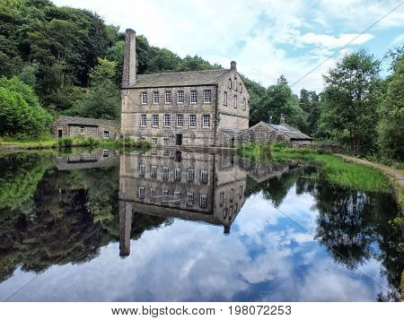 gibson mill a water powered mill with main bulding relected in the pond and surroounding trees of hardcastle crags near hebden bridge in west yorkshire