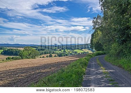 Undulating, uneven terrain covered with leaf clumps of deciduous trees. Two slopes descending into a deep valley. In the valley you can see the buildings. On the right side of the road. In the distance you see the steep hills, It is sunny day. The sky is