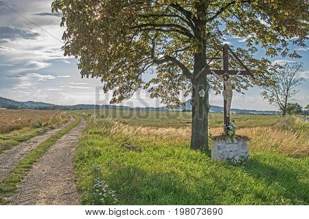 Standing on the dirt road cross. The road is on the left. The fields are agricultural. On the cross is the image of Jesus. Behind the cross is the tree on which the chapel is located. In the distance you can see wooded hills. It is sunny day.