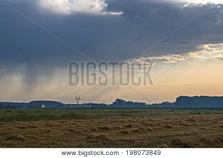 There is a dark, rainy cloud in the sky. On the right side of the cloud is the sun shining. On the left you can see dark streaks of rain falling. At the bottom is arable field.